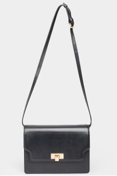 Черная кожаная сумка прямоугольной формы с биркой