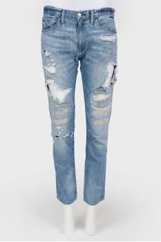 Синие джинсы с потертостями и декоративными прорезями